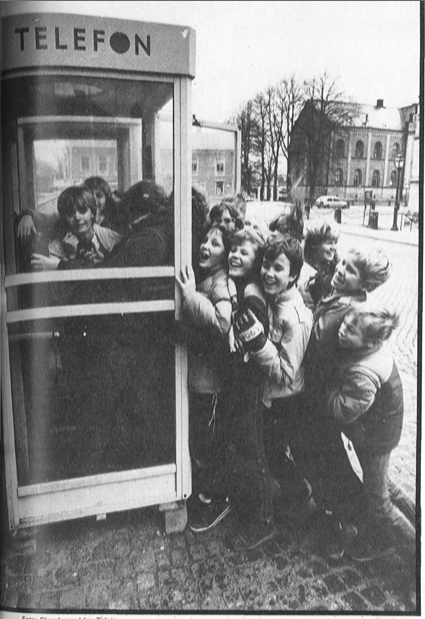 Barn i telefonkiosk